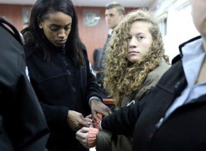 Palestinian teen Ahed Tamimi (R) enters a military courtroom escorted by Israeli Prison Service personnel at Ofer Prison, near the West Bank city of Ramallah, January 1, 2018. REUTERS/Ammar Awad