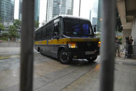 """A prison van arrives as journalists wait for Tong Ying-kit's arrival at the Hong Kong High Court in Hong Kong Friday, July 30, 2021. Tong was convicted Tuesday of inciting secession and terrorism for driving his motorcycle into a group of police officers during a July 1, 2020, pro-democracy rally while carrying a flag bearing the banned slogan, """"Liberate Hong Kong, revolution of our times."""" Tong, 24, will be sentenced Friday, the court announced. (AP Photo/Vincent Yu)"""
