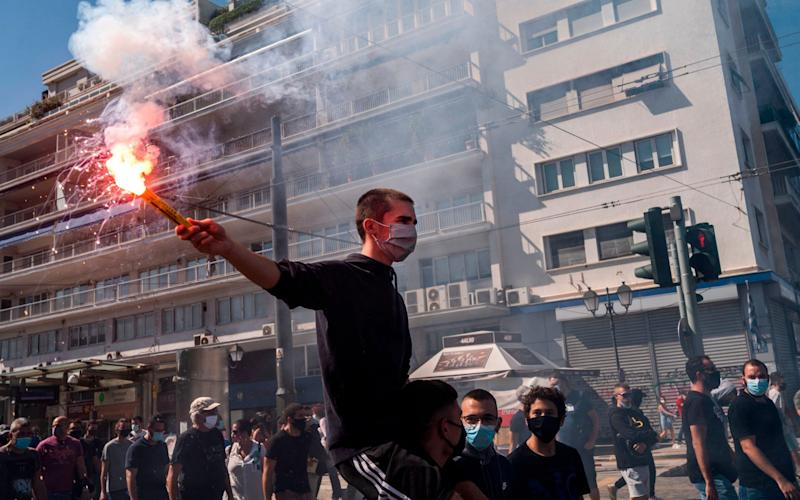 A protester holds a burning flare during a demonstation over the risks of coronavirus in schools in Athens - AFP