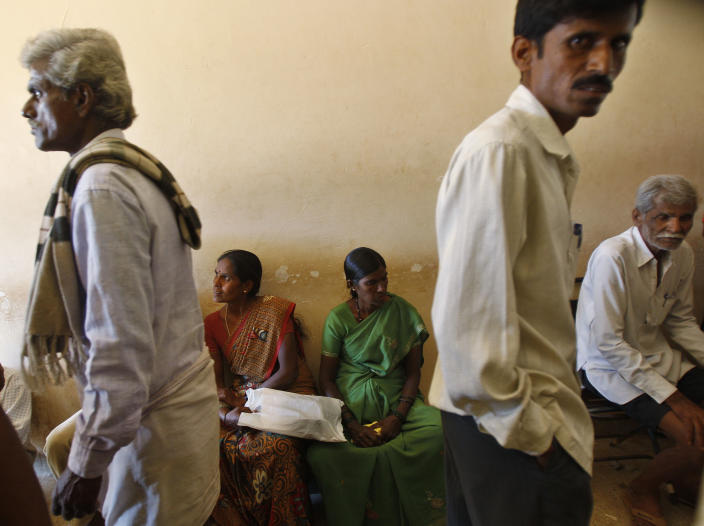 In this Dec.10, 2012 photo, people wait to get their land registered at the government registrar's office in Hoskote 30 kilometers (19 miles) from Bangalore in the southern Indian state of Karnataka. For years, Karnataka's land records were a quagmire of disputed, forged documents maintained by thousands of tyrannical bureaucrats who demanded bribes to do their jobs. In 2002, there were hopes that this was about to change. (AP Photo/Aijaz Rahi)