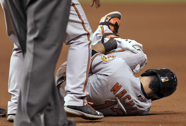 Baltimore Orioles' Manny Machado grabs his left leg after it buckled while he was running to first base on a seventh-inning single off Tampa Bay Rays relief pitcher Jake McGee during a baseball game Monday, Sept. 23, 2013, in St. Petersburg, Fla. Machado had was taken off the field on a stretcher. (AP Photo/Chris O'Meara)