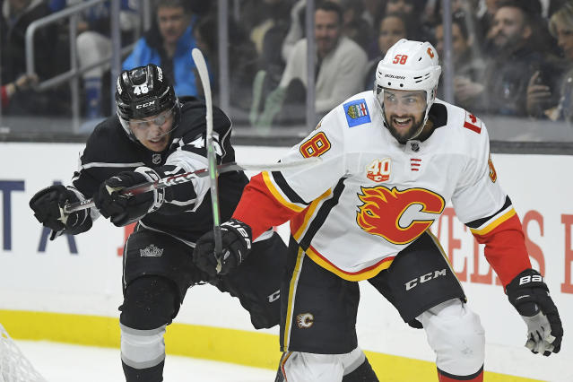 Los Angeles Kings center Blake Lizotte, left, reaches out to hook Calgary Flames defenseman Oliver Kylington during the second period of an NHL hockey game Wednesday, Feb. 12, 2020, in Los Angeles. (AP Photo/Mark J. Terrill)