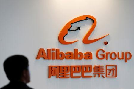 A man stands near the logo of Alibaba Group at the company's newly-launched office in Kuala Lumpur