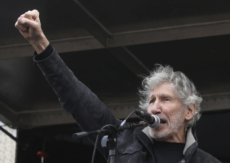 Former Pink Floyd bass player Roger Waters speaks to crowds gathered at Parliament Square in London, protesting against the imprisonment and extradition of Wikileaks founder Julian Assange  extradition, Saturday Feb. 22, 2020.  (Isabel Infantes/PA via AP)