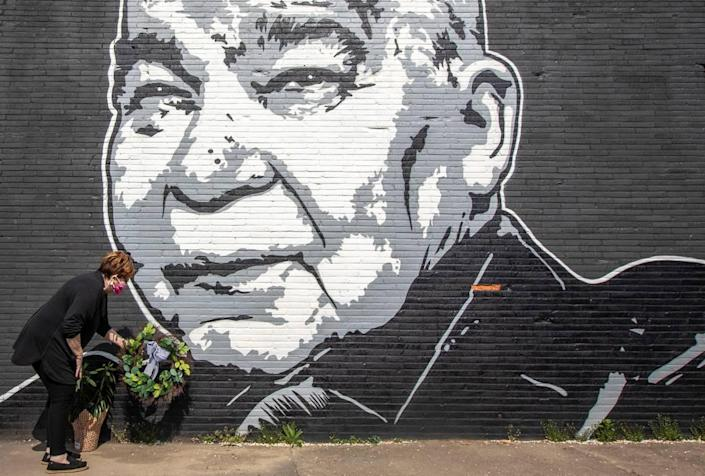Maribeth Schmitt, of Lexington, places a wreath below a mural of singer John Prine, on the side of Apollo's Pizza on Leestown Road in Lexington, on Wednesday, April 8, 2020. Prine, 73, died Tuesday at Nashville's Vanderbilt University Medical Center following complications brought on by COVID-19. The mural was painted by Graham Allen of SquarePegs Studio and Design.