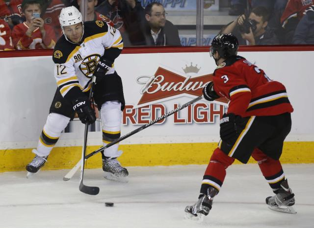 Calgary Flames' Ladislav Smid stick checks Boston Bruins' Jarome Iginla during first period NHL in Calgary, Alta., Tuesday, Dec. 10, 2013. (AP Photo/The Canadian Press, Jeff McIntosh)