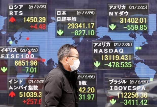 A man walks past a stock quotation board at a brokerage in Tokyo on Friday. Markets tumbled Thursday and were down again Friday — paradoxically, on news of a strengthening economy.  (Kim Kyung-Hoon/Reuters - image credit)