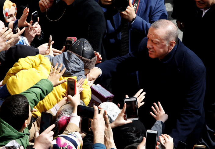 A boy kisses the hand of Turkey's President Recep Tayyip Erdogan outside of a polling station during local elections, in Istanbul, Sunday, March 31, 2019. Mayoral elections are underway in 30 large cities in Turkey along with other municipal races Sunday that are seen as a barometer of President Recep Tayyip Erdogan's popularity amid a sharp economic downturn in the nation straddling Europe and Asia. (AP Photo/Lefteris Pitarakis)