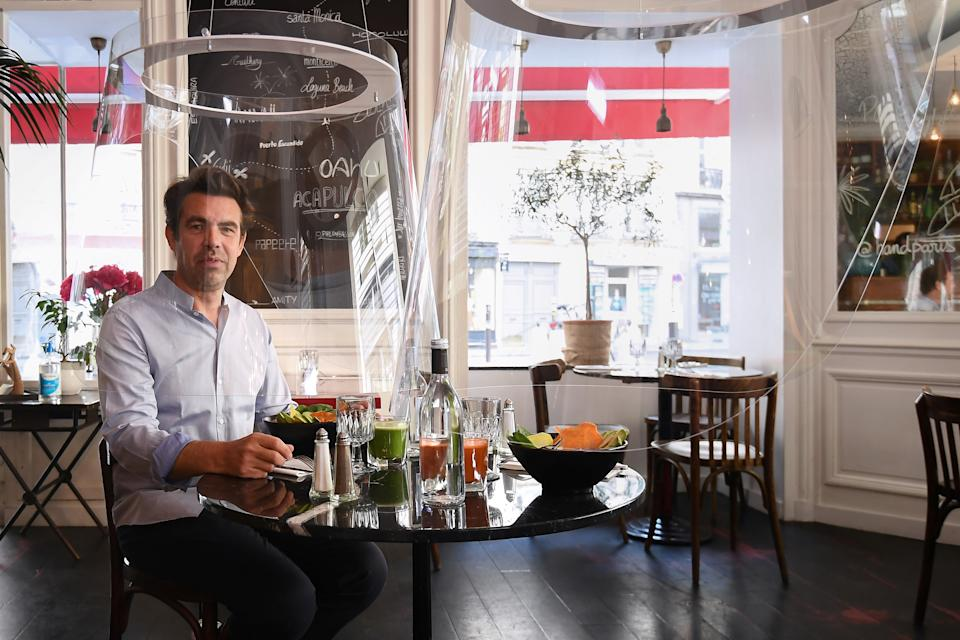 French designer Christophe Gernigon poses under one of the plexiglas protections he designed, at the H.A.N.D restaurant on May 27, 2020 in Paris, as France eases lockdown measures taken to curb the spread of the COVID-19 pandemic, caused by the novel coronavirus. (Photo by ALAIN JOCARD / AFP) (Photo by ALAIN JOCARD/AFP via Getty Images)