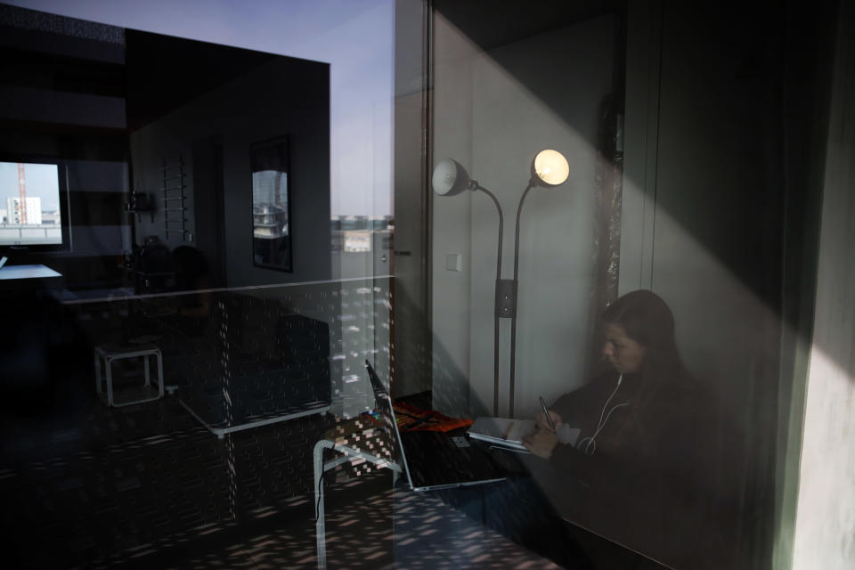Lina Maria Fajardo of Colombia, a student in psychiatry of elderly people is seen through a window as she studies in her student housing in Ivry sur Seine, outside Paris, Thursday, Feb. 11, 2021. A quarter of French young professionals can't find work, and many university students are standing in food lines or calling hotlines for psychological help. They are France's future, and their plight is central to the country's battle to emerge from the pandemic. (AP Photo/Christophe Ena)
