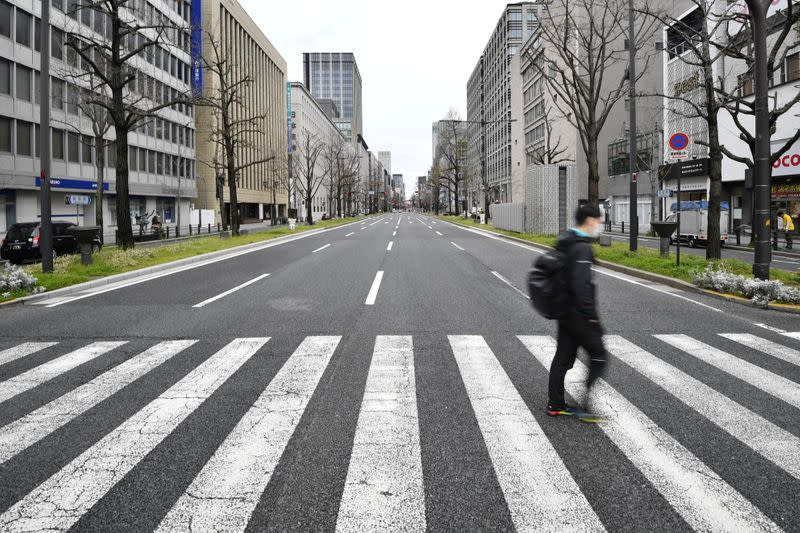A man wearing a protective face mask, following an outbreak of the coronavirus disease, walks on a nearly empty street in Osaka