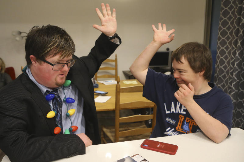 In this Monday, Dec. 9, 2019, photo, Luke Humble, right, and Conor Gunderson, left, high-five one another as they think about their grocery list in the kitchen at the new Luna Azul housing development for adults with disabilities, in Phoenix. Parents in Arizona, Wisconsin, Maryland and other states have launched housing developments for adults with disabilities in recent years. (AP Photo/Ross D. Franklin)