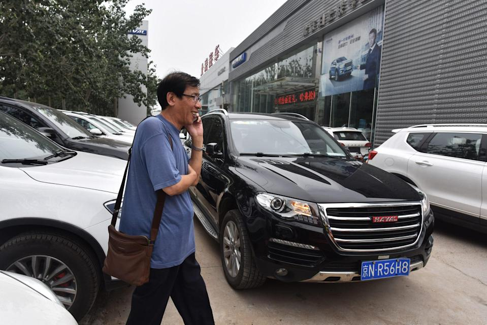 A man walks past Haval brand SUVs made by China's Great Wall Motor. The company's shares rose after media reports said that smartphone maker Xiaomi plans to make cars at its factory. Photo: AFP