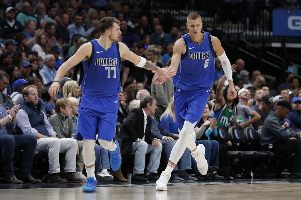 FILE - In this Oct. 27, 2019, file photo, Dallas Mavericks' Luka Doncic (77) and Kristaps Porzingis (6) celebrate a basket by Porzingis in the second half of an NBA basketball game against the Portland Trail Blazers in Dallas. The NBA restart means Doncic and Porzingis are all but assured of making their playoff debuts in their first season on the court together with Dallas. (AP Photo/Tony Gutierrez, File)