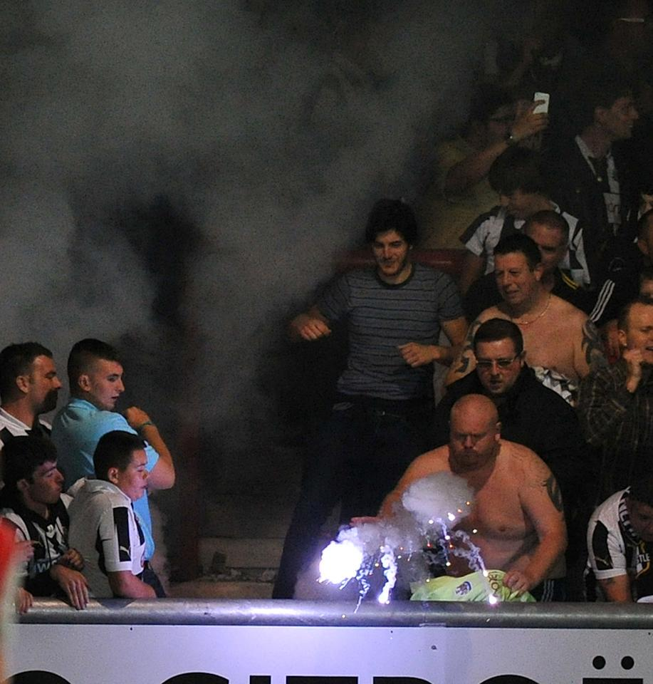 A Newcastle United fan throws a flare onto the pitch in celebration of the first goal during the Capital One Cup, Second Round match at the Globe Arena, Morecambe.