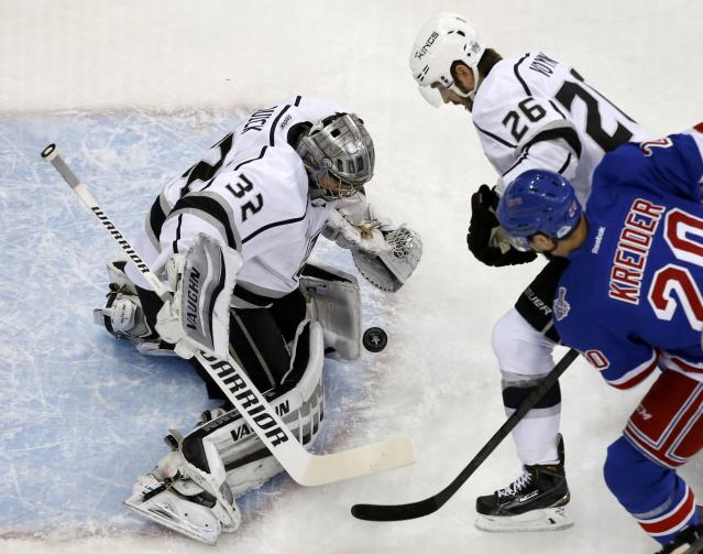 Los Angeles Kings goalie Jonathan Quick (L) makes a save on New York Rangers' Chris Kreider as King's Slava Voynov attempts to clear the front of the crease during the first period in Game 4 of their NHL Stanley Cup Finals hockey series in New York June 11, 2014. REUTERS/Shannon Stapleton (UNITED STATES - Tags: SPORT ICE HOCKEY)