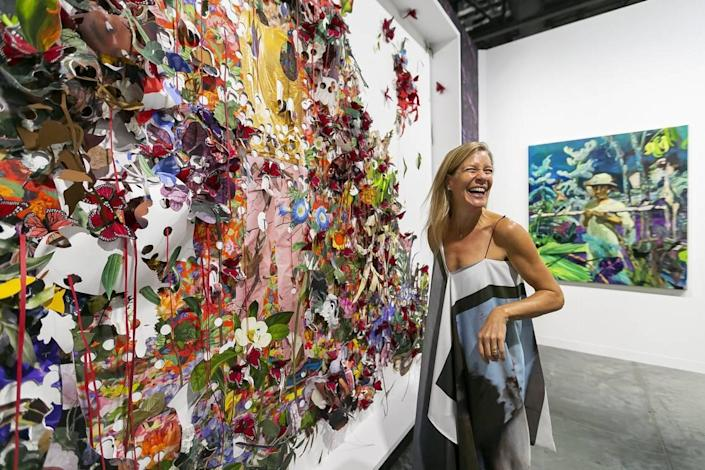 Kathryn Mikesell, an art collector and an art patron, looks at work by Ebony G. Patterson and Maia Cruz Palileo during Art Basel at the Miami Beach Convention Center on Wednesday, December 4, 2019.