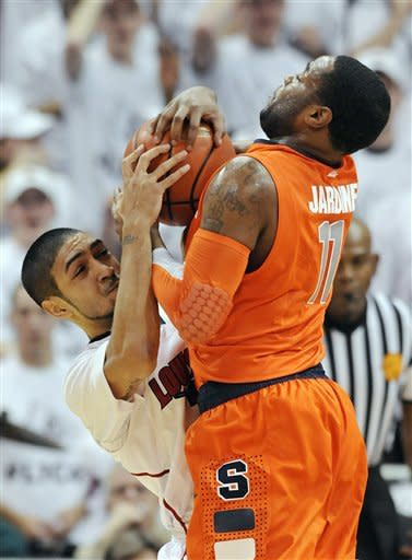 Louisville's Peyton Siva, left, battles Syracuse's Scoop Jardine (11) for a loose ball during the first half of their NCAA college basketball game, Monday, Feb. 13, 2012, in Louisville, Ky. (AP Photo/Timothy D. Easley)