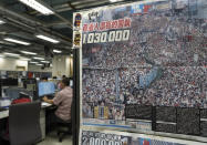 An Apple Daily front page showing the number of a march is displayed at the news room of Apple Daily Monday, April 26, 2021. A newspaper that has advocated for greater democracy in Hong Kong came under further pressure Thursday, June 17, 2021, with the arrests of three top editors and two senior executives.(AP Photo/Vincent Yu)