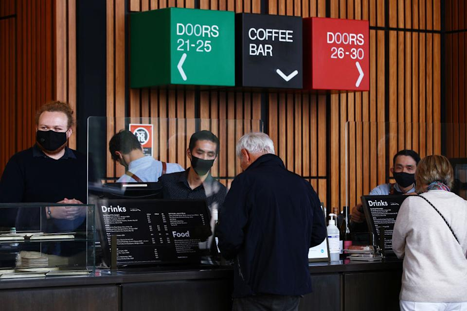 Staff are seen wearing face masks as they serve guests on arrival for the Don Burrows: A Celebration of Life Through Jazz show in the Joan Sutherland Theatre at the Sydney Opera House.