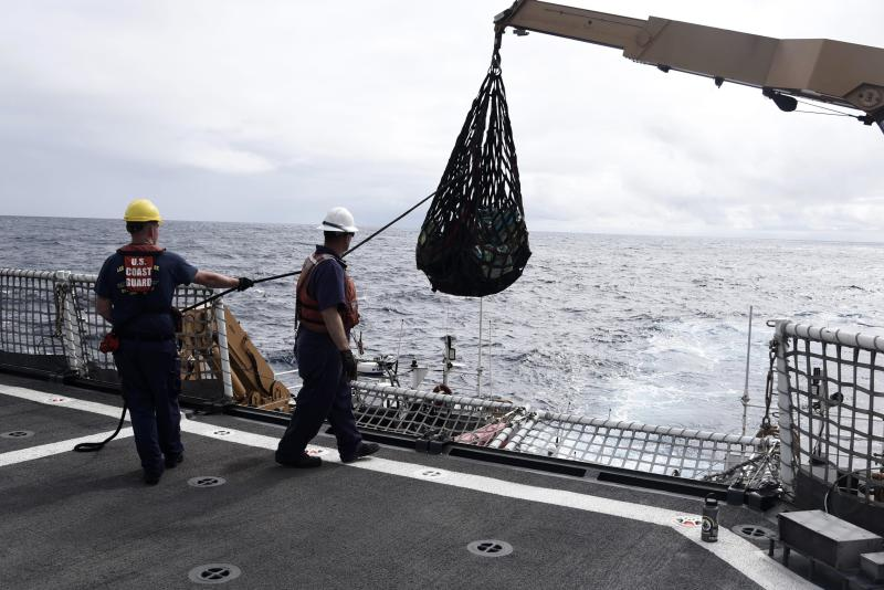In this Nov. 4, 2019 photo provided by the U.S. Coast Guard, Coast Guard Cutter Bertholf crew members use a crane and cargo net to transfer bales of contraband from Bertholf's 35-foot Long Range Interceptor boat to the cutter following an at-sea interdiction of a low-profile go-fast vessel during Bertholf's patrol to the Eastern Pacific Ocean. An estimated $312 million worth of cocaine seized from smugglers in the eastern Pacific Ocean has been brought to San Diego. About 18,000 pounds (8,165 kilograms) of the drug was offloaded Wednesday, Dec. 18, 2019, from the Coast Guard cutter Bertholf. (Petty Officer 2nd Class Paul Krug/U.S. Coast Guard via AP)
