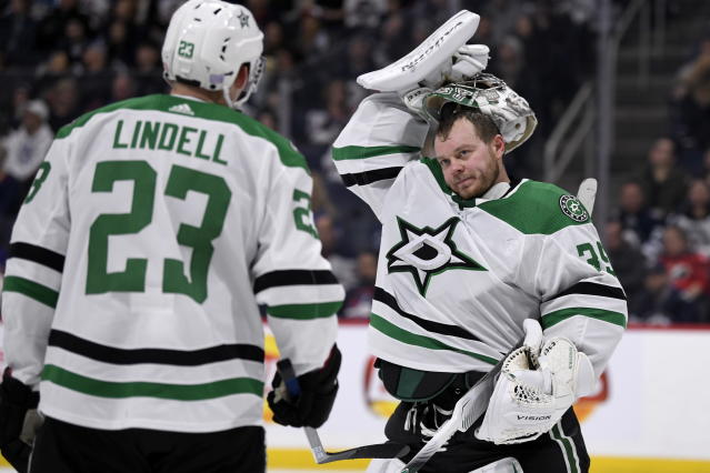 Dallas Stars goaltender Anton Khudobin (35) talks to Esa Lindell (23) during a break in second-period NHL hockey game action against the Winnipeg Jets in Winnipeg, Manitoba, Sunday, Nov. 10, 2019. (Fred Greenslade/The Canadian Press via AP)