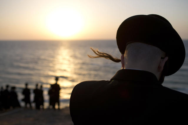 <p>Ultra-Orthodox Jews of the Hassidic sect Vizhnitz gather on a hill overlooking the Mediterranean sea as they participate in a Tashlich ceremony in Herzeliya, Israel, Sept. 12, 2013. (Photo: Oded Balilty/AP) </p>