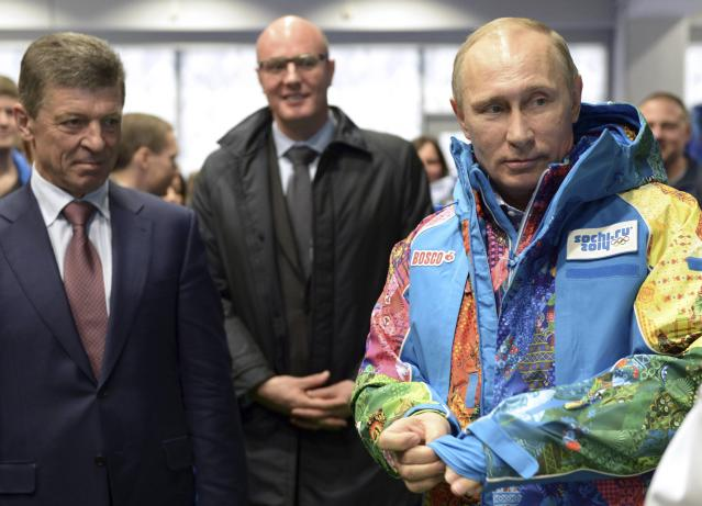 Russia's President Vladimir Putin (R), Organising Committee Head Dmitry Chernyshenko (C) and Deputy Prime Minister Dmitry Kozak (L) visit an Olympic volunteers centre in Sochi January 4, 2014. Putin has eased curbs on demonstrations in the Winter Olympics venue of Sochi in a gesture likely to burnish Russia's image ahead of an event dogged by security and human rights worries. REUTERS/Alexei Nikolskiy/RIA Novosti/Kremlin (RUSSIA - Tags: POLITICS SPORT OLYMPICS) ATTENTION EDITORS - THIS IMAGE HAS BEEN SUPPLIED BY A THIRD PARTY. IT IS DISTRIBUTED, EXACTLY AS RECEIVED BY REUTERS, AS A SERVICE TO CLIENTS