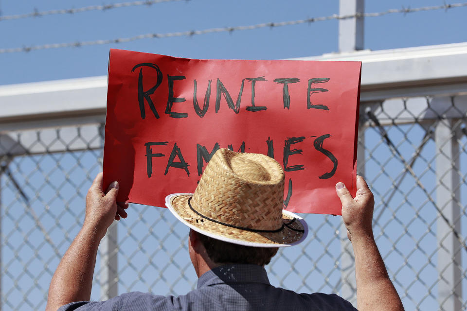 FILE - In this June 21, 2018 file photo, a protester holds a sign outside a closed gate at the Port of Entry facility in Fabens, Texas, where tent shelters were being used to house separated family members. The Biden administration is stepping up its effort to find and unite migrant families forcibly separated under President Donald Trump. (AP Photo/Matt York)