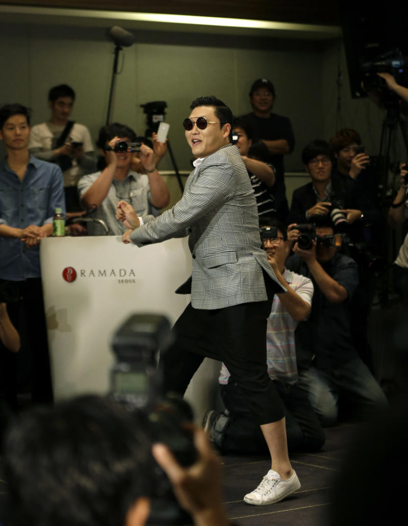 """South Korean rapper PSY, who sings the popular """"Gangnam Style"""" song, dances as he leaves his press conference in Seoul, South Korea, Tuesday, Sept. 25, 2012. (AP Photo/Lee Jin-man)"""