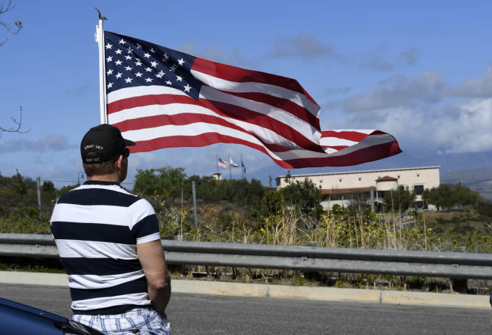 <p>Andy Hall of Simi Valley pays his respects by holding a flag near the Ronald Reagan Presidential Library.<i> (Photo: Mark J. Terrill/AP)</i></p>
