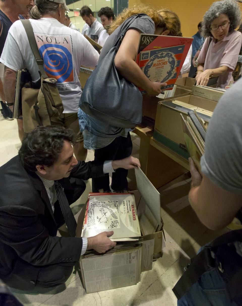 "Eli Zimmerman, lower left, who says he has ""a record addiction,"" kneels as he browses his selections at the New York City Public Library for the Performing Arts at Lincoln Center, Friday, Aug. 9, 2013. The library is selling 22,000 duplicate vinyl records that were preserved in mint condition to raise money for the expansion of the library. (AP Photo/Richard Drew)"