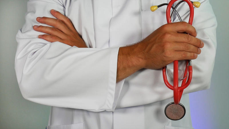 Person in lab coat holding a red stethoscope.