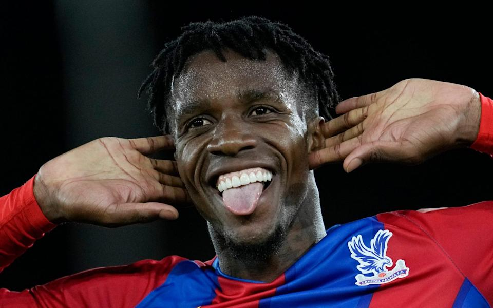 Crystal Palace's Wilfried Zaha celebrates after he scored his side's first goal during the English Premier League soccer match between Crystal Palace and Brighton - AP Photo/Matt Dunham