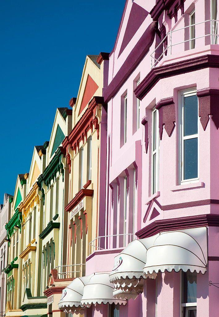 <p>Pastel homes with complementary trim are coordinated on the streets of England.</p>