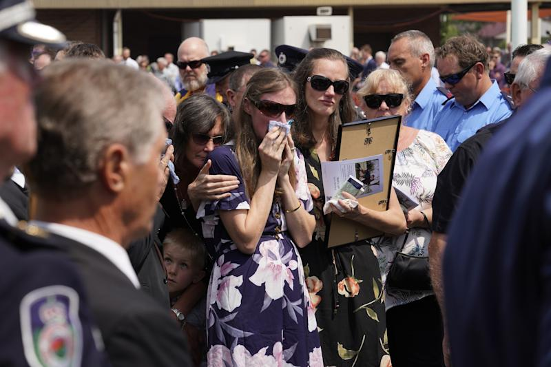 Samuel McPaul's widow Megan wipes away tears as she watches the casket being loaded into the hearse.