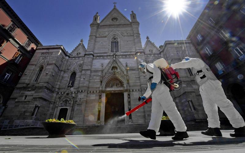 Members of the Italian Armed Forces in protective gear disinfect the area outside the Cathedral of Naples - Shutterstock