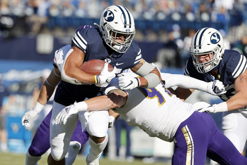 BYU running back Tyler Allgeier (25) runs the ball for a touchdown in the first quarter against North Alabama defensive lineman Charlie Ryan (92) during an NCAA college football game Saturday, Nov. 21, 2020, in Provo, Utah. (AP Photo/Jeff Swinger, Pool)