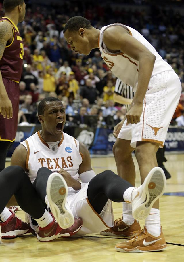 Texas forward Jonathan Holmes, left, reacts to being fouled as Demarcus Holland looks on during the second half of a second-round game against the Arizona State in the NCAA college basketball tournament Thursday, March 20, 2014, in Milwaukee. (AP Photo/Morry Gash)