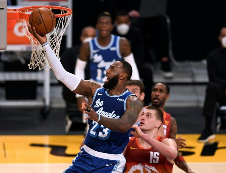 Los Angeles Lakers LeBron James scores on a layup past Nikola Jokic, 15, of the Denver Nuggets during the first half of their NBA game at Staples Center