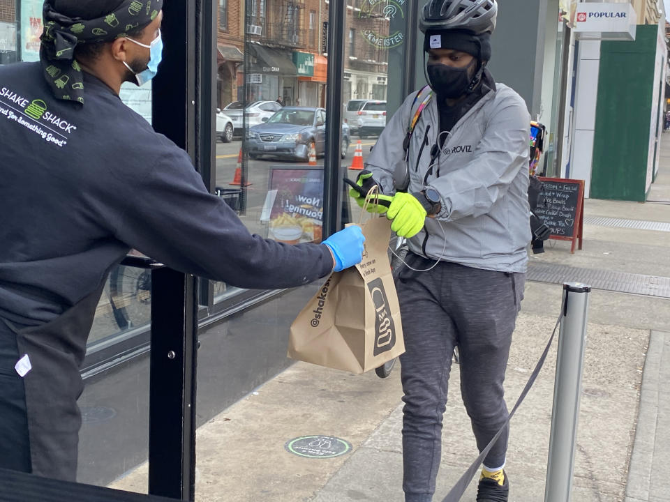 Shake Shack employee handing off food to delivery person, Queens, New York. (Photo by: Lindsey Nicholson/Education Images/Universal Images Group via Getty Images)