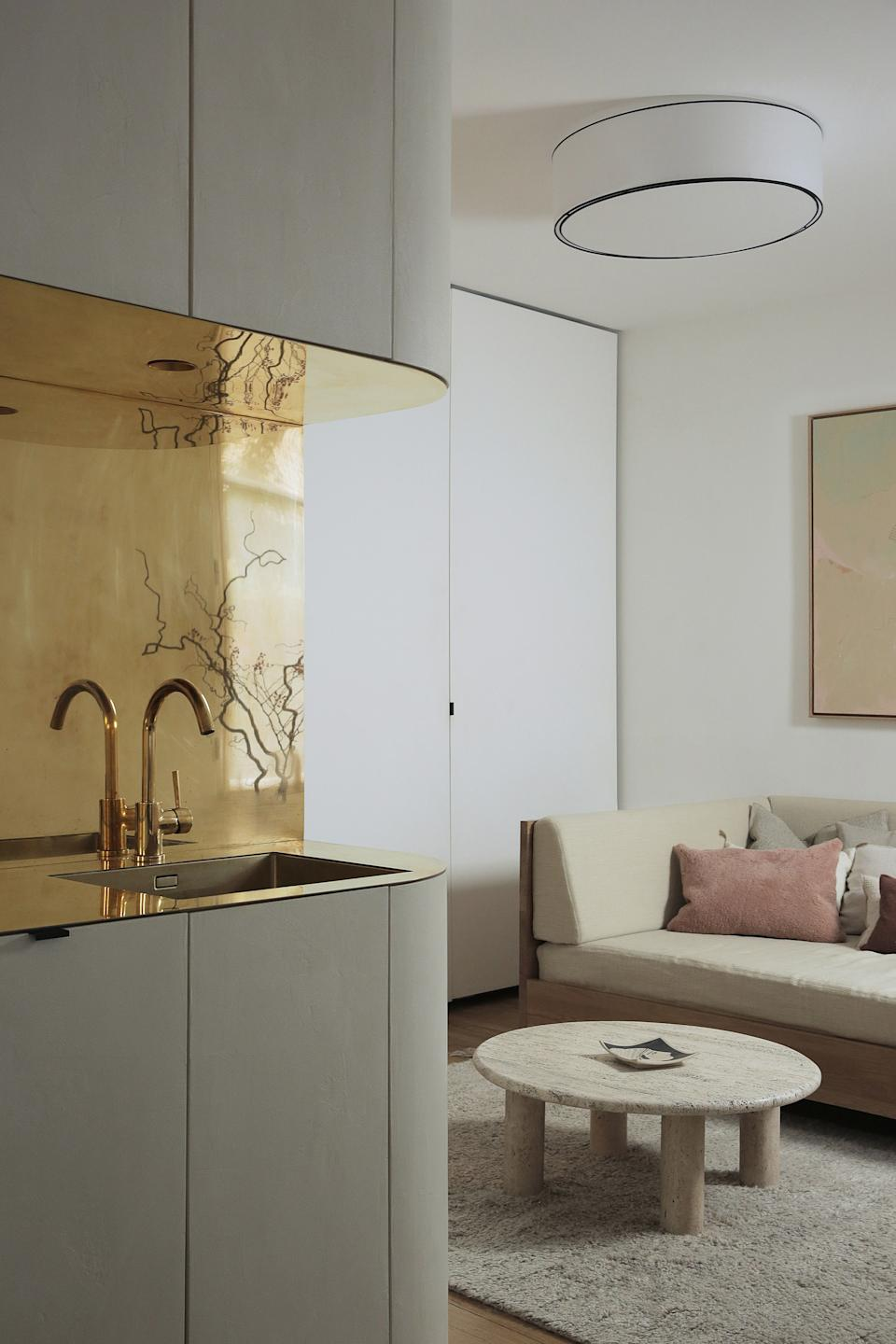 """<div class=""""caption""""> On the other side of the space is a sleeping area with a daybed dressed with oatmeal-colored linen bedding that matches the cushions on the dinette that continue the warm, neutral tones and natural textures. </div>"""