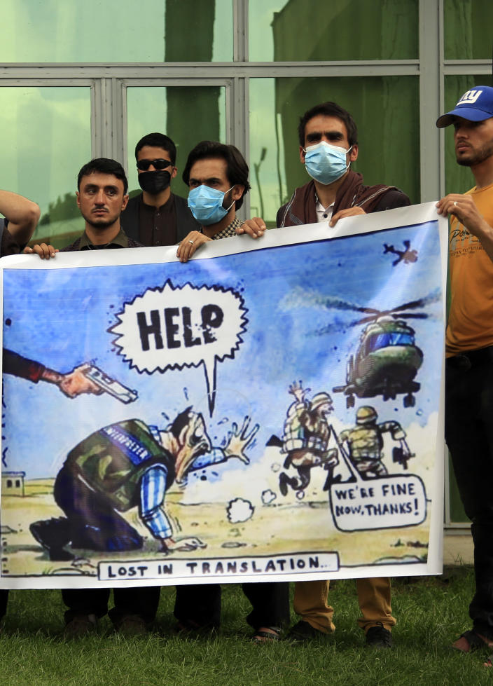 In this Friday, April 30, 2021, photo former Afghan interpreters hold banner during a protest against the U.S. government and NATO in Kabul, Afghanistan. (AP Photo/Mariam Zuhaib)