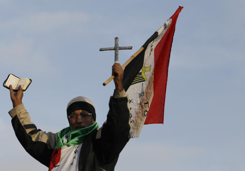 An Egyptian protester holds the Quran, Islam's hold book, a Cross, and the Egyptian national flag during a demonstration in front of the presidential palace in Cairo, Egypt, Tuesday, Dec. 11, 2012. Thousands of opponents and supporters of Egypt's Islamist president were flocking to key locations in the nation's capital ahead of rival mass rallies Tuesday, four days before a nationwide referendum on a contentious draft constitution. (AP Photo/Petr David Josek)