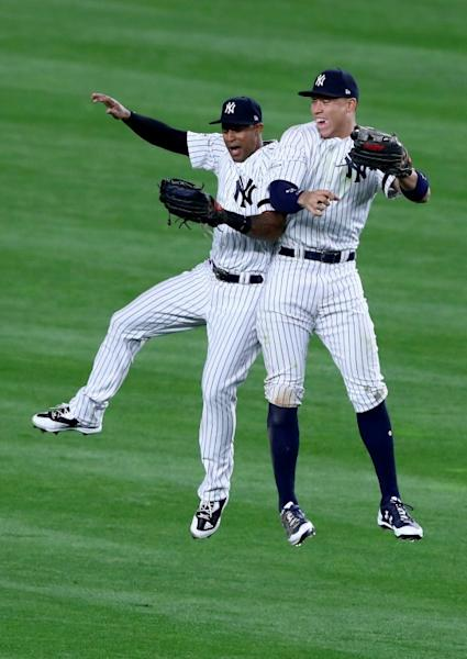Aaron Judge (R) of the New York Yankees celebrates with teammate Aaron Hicks after defeating the Houston Astros in Game Three of the American League Championship Series, at Yankee Stadium in York, on October 16, 2017
