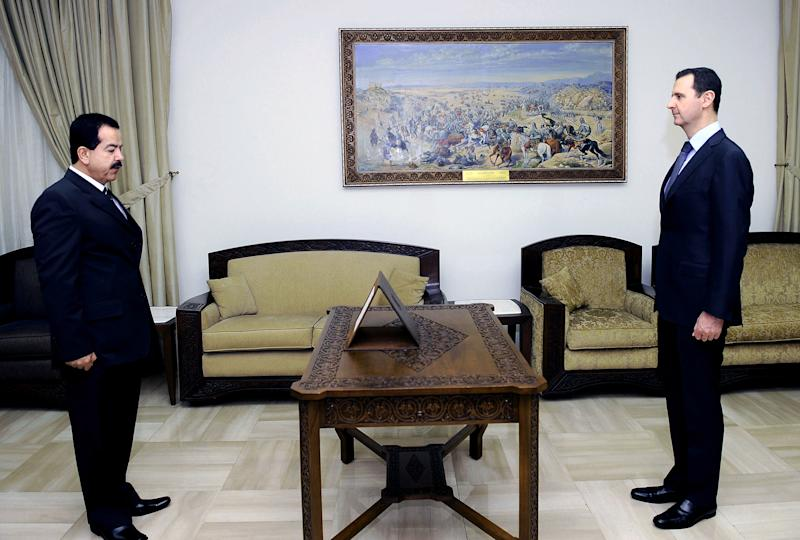 In this photo released by the Syrian official news agency SANA, Ahmed Sheikh Abdul Qadir, left, is sworn in as governor of Latakia province, by Syrian President Bashar Assad, right, in Damascus, Syria, Sunday, June 2, 2013. (AP Photo/SANA)
