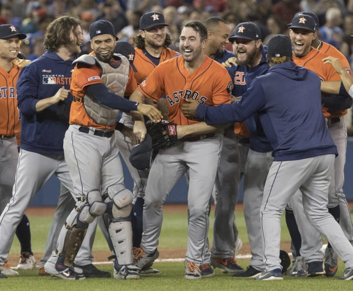 Houston Astros starting pitcher Justin Verlander, center, is mobbed by teammates after pitching a no-hitter against the Toronto Blue Jays in a baseball game in Toronto, Sunday, Sept. 1, 2019. (Fred Thornhill/The Canadian Press via AP)