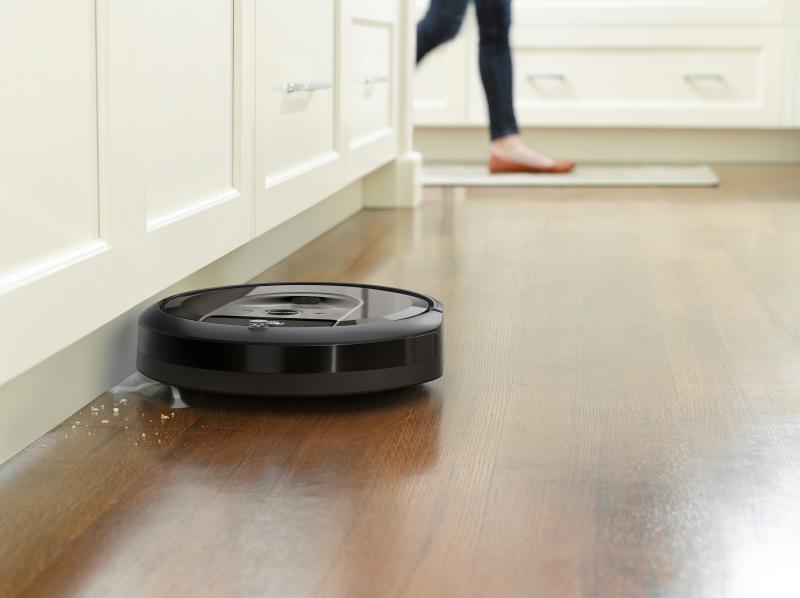Roomba i7 sweeping crumbs from along a baseboard on a wood floor