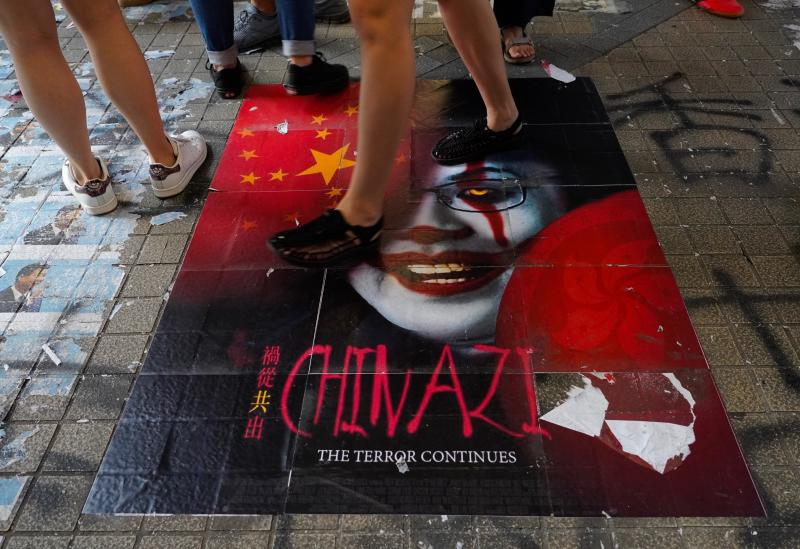 Pedestrians step on a caricature of Hong Kong Chief Executive Carrie Lam, part of a newly created Lennon Wall in Hong Kong, Saturday, Sept. 28, 2019. Hong Kong activists first created their own Lennon Wall during the 2014 protests, covering a wall with a vibrant Post-it notes calling for democratic reform. Five years later, protestors have gathered to create impromptu Lennon Walls across Hong Kong island. (AP Photo/Vincent Yu)