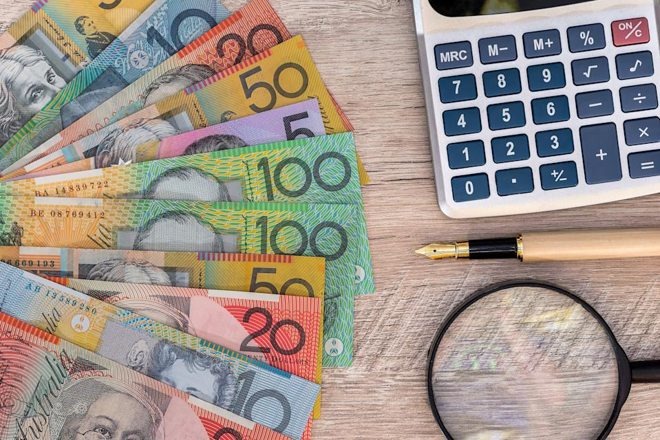 Australian dollars with calculator, pen and magnifier. Tax concept.
